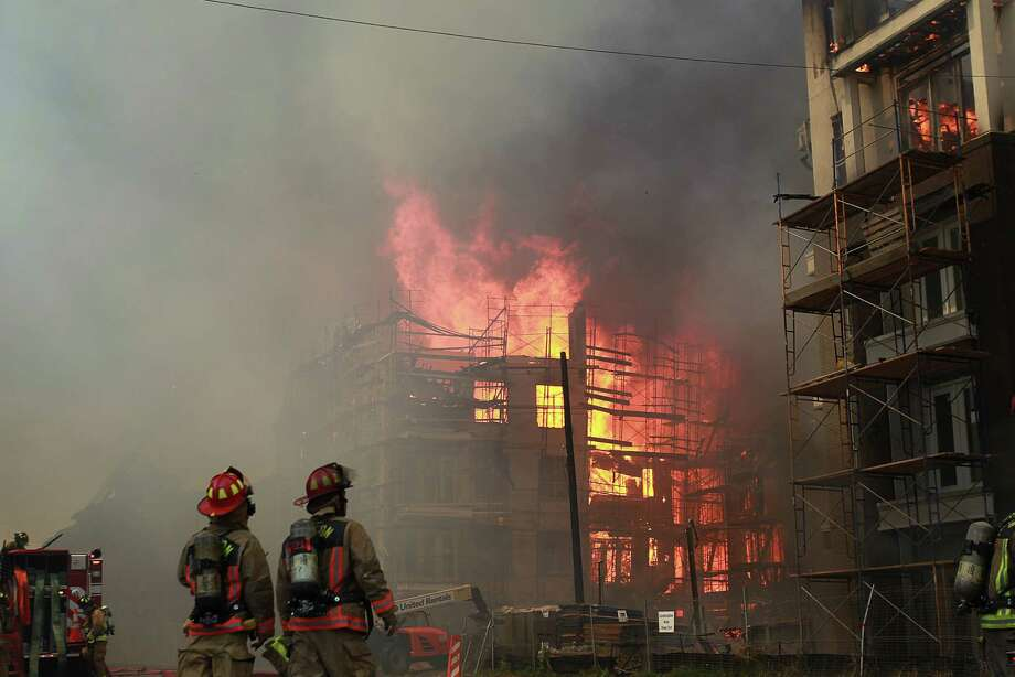A second building under construction catches fire as HFD attempts to extinguish fire at the corner of Marconi St. and Dallas Ave. on March 25, 2014, in Houston, Tx. Photo: Mayra Beltran, Houston Chronicle / © 2014 Houston Chronicle