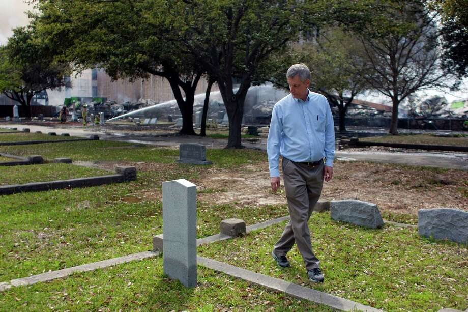 Glen Telge, president of the Magnolia Cemetery of Houston walks past a gravestone in the cemetery as firefighters battled a large 5-alarm blaze Tuesday afternoon at an apartment building under construction on West Dallas near Montrose Tuesday, March 25, 2014, in Houston. Flames engulfed the apartment complex as 200 firefighters in 80 units fought to gain an upper hand on the blaze. The five-story, 368-unit building was destroyed. No injuries were reported. Photo: Johnny Hanson, Houston Chronicle / © 2014  Houston Chronicle