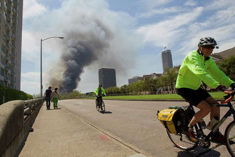 Cyclist ride down Studewood as firefighters battled a large 5-alarm blaze Tuesday afternoon at an apartment building under construction on West Dallas near Montrose Tuesday, March 25, 2014, in Houston. Flames engulfed the apartment complex as 200 firefighters in 80 units fought to gain an upper hand on the blaze. The five-story, 368-unit building was destroyed. No injuries were reported. Photo: Johnny Hanson, Houston Chronicle / © 2014  Houston Chronicle