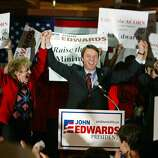 Democratic presidential hopeful Sen. John Edwards, D-N.C., center, raises his arms with state Board of Equalization Chairwoman Carole Migden, left, and state Assemblyman Leland Yee, right, after giving a campaign speech at the Delancey Street Auditorium in San Francisco, Thursday Feb. 26, 2004.