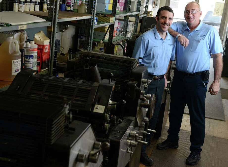 Frank Halpin and his son Andrew stand near a row of printing presses at EverReady Press Wednesday, Mar. 26, 2014, in Ansonia, Conn. The family owned business is celebrating its 85th year. Photo: Autumn Driscoll / Connecticut Post