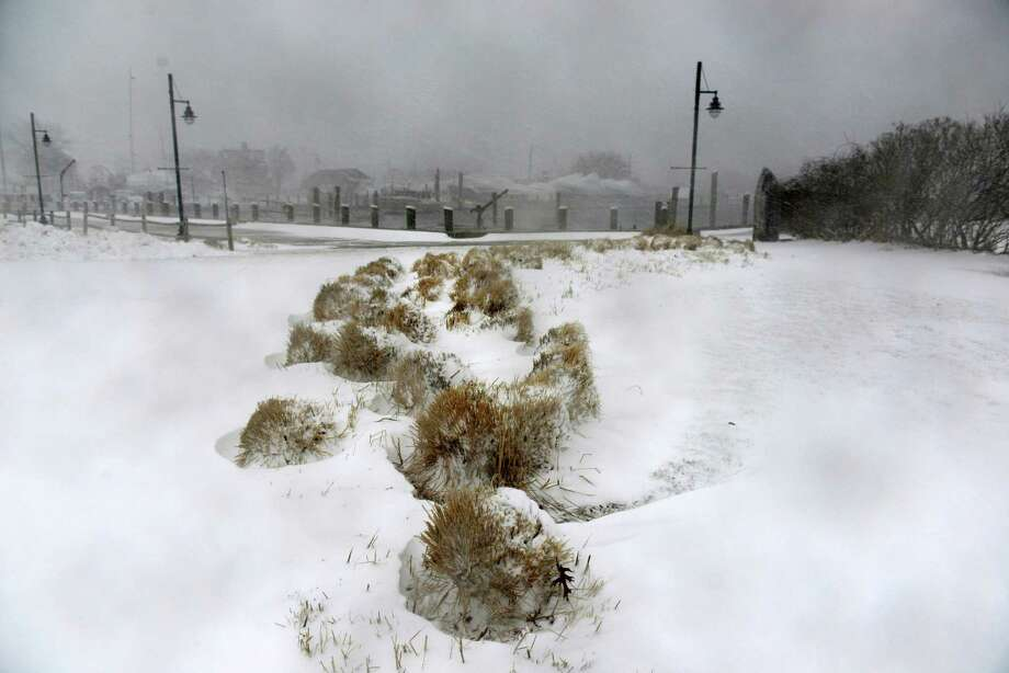 Snow covered grass lies near the harbor during a spring snowstorm March 26, 2014 in Hyannis, Massachusetts. An early spring storm brought high winds and some snow accumulation, with blizzard conditions expected to last throughout the morning. Photo: Darren McCollester, Getty Images / 2014 Getty Images