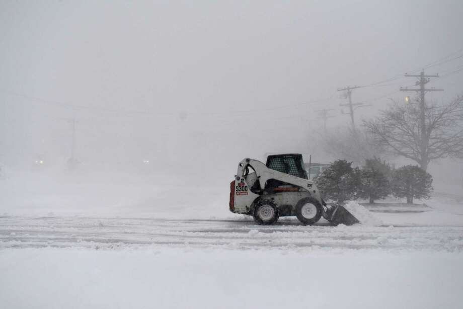 A snowplow clears a parking lot on North Street during a snowstorm March 26, 2014 in Hyannis, Massachusetts. An early spring storm brought high winds and some snow accumulation, with blizzard conditions expected to last throughout the morning. Photo: Darren McCollester, Getty Images / 2014 Getty Images