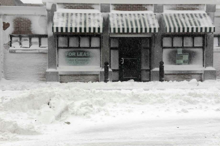 Buildings along Main Street are seen covered with snow during a snowstorm March 26, 2014 in Hyannis, Massachusetts. An early spring storm brought high winds and some snow accumulation, with blizzard conditions expected to last throughout the morning. Photo: Darren McCollester, Getty Images / 2014 Getty Images