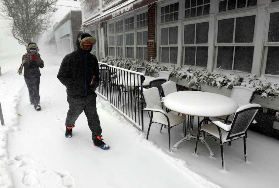 People walk down Main Street past snow covered tables and chairs during a snowstorm March 26, 2014 in Hyannis, Massachusetts. An early spring storm brought high winds and some snow accumulation, with blizzard conditions expected to last throughout the morning. Photo: Darren McCollester, Getty Images / 2014 Getty Images