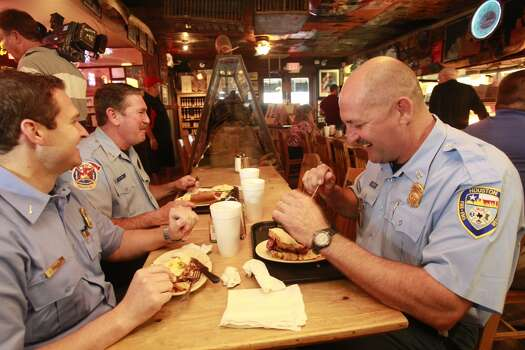 "Houston Fire Dept. Capt. Jake Sandlin, left, Engine Operator Dwayne Wyble , center, and Senior Capt. Brad Hawthorne, Right, eat at Goode Company, 5109 Kirby Dr., where they paid for their meals despite the restaurant offering free BBQ sandwiches all day to HFD members Wednesday, March 26, 2014 in Houston. Wyble was operating the ladder that Capt. Hawthorne was on when he was captured on video rescuing a worker who was trapped by yesterday's apartment fire. Speaking about grabbing the man who jumped from a balcony onto the ladder, Capt. Hawthrone said, ""just another day at the office."" (Melissa Phillip / Houston Chronicle)   Photo: Melissa Phillip, Houston Chronicle"