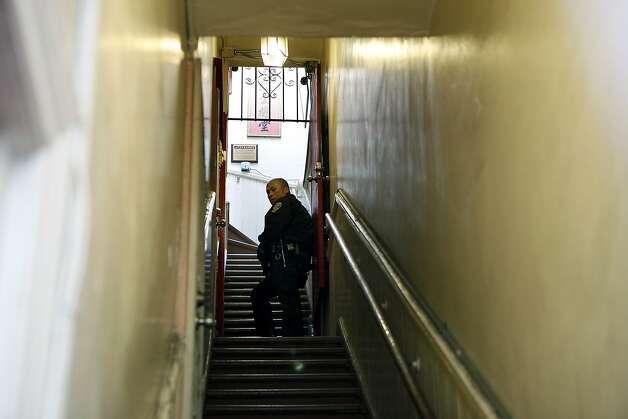 An SFPD officer guards the stairwell of the Ghee Kung Tong Chinese Free Masons Temple in Chinatown during a raid related to Sen. Leland Yee's arrest, San Francisco, CA, Wednesday Mar. 26, 2014.  The FBI raids State Sen. Leland Yee's office in Sacramento and other locations were searched by the FBI in San Francisco. He was reportedly arrested on public corruption charges Wednesday morning amid raids of his office in Sacramento and searches by the FBI in San Francisco. Photo: Michael Short, The Chronicle
