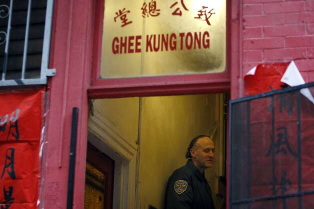 An SFPD officer stands in the doorway of the Ghee Kung Tong Chinese Free Masons Temple in Chinatown during a raid related to Sen. Leland Yee's arrest, San Francisco, CA, Wednesday Mar. 26, 2014.  The FBI raids State Sen. Leland Yee's office in Sacramento and other locations were searched by the FBI in San Francisco. He was reportedly arrested on public corruption charges Wednesday morning amid raids of his office in Sacramento and searches by the FBI in San Francisco. Photo: Michael Short, The Chronicle
