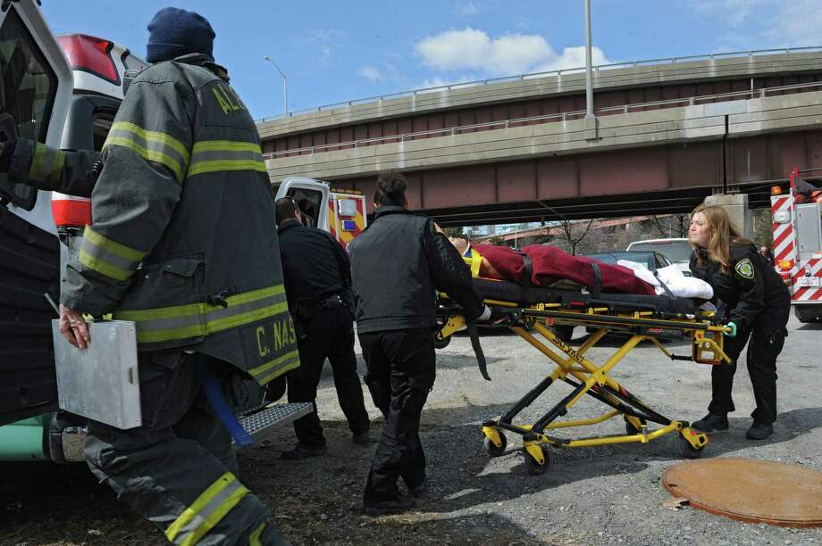 Emergency workers load a man who jumped off the Dunn Memorial Bridge after a long car chase on Wednesday, March 26, 2014, in Rensselaer, N.Y. (Lori Van Buren / Times Union) Photo: Lori Van Buren / 00026284A