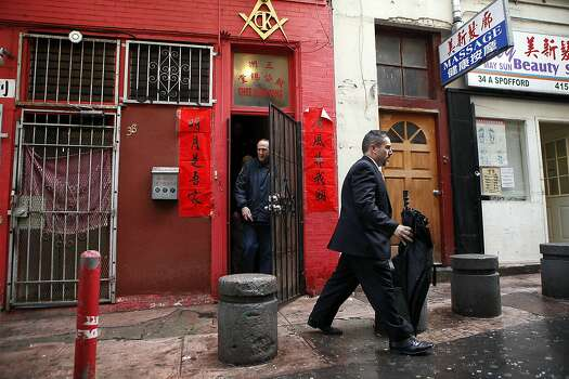 FBI Special Agent Michael Gimbel, right, leaves the Ghee Kung Tong Chinese Free Masons Temple in Chinatown that was the target of a raid related to Sen. Leland Yee's arrest, San Francisco, CA, Wednesday Mar. 26, 2014.  The FBI raids State Sen. Leland Yee's office in Sacramento and other locations were searched by the FBI in San Francisco. He was reportedly arrested on public corruption charges Wednesday morning amid raids of his office in Sacramento and searches by the FBI in San Francisco. Photo: Michael Short, The Chronicle