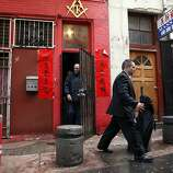 FBI Special Agent Michael Gimbel, right, leaves the Ghee Kung Tong Chinese Free Masons Temple in Chinatown that was the target of a raid related to Sen. Leland Yee's arrest, San Francisco, CA, Wednesday Mar. 26, 2014.  The FBI raids State Sen. Leland Yee's office in Sacramento and other locations were searched by the FBI in San Francisco. He was reportedly arrested on public corruption charges Wednesday morning amid raids of his office in Sacramento and searches by the FBI in San Francisco.