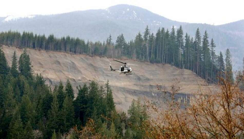 A helicopter flies past the area where a deadly mudslide hit on Saturday, Tuesday in Arlington. Phot