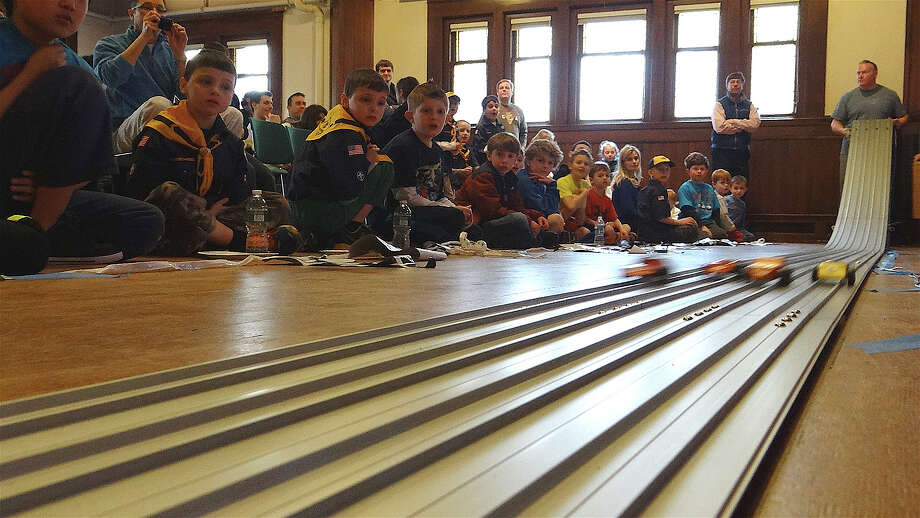 Members of Mill Hill School's Cub Scout Pack 98 cheer on their racers in the group's Pinewood Derby on Saturday in the Pequot Library. Photo: Mike Lauterborn / Fairfield Citizen