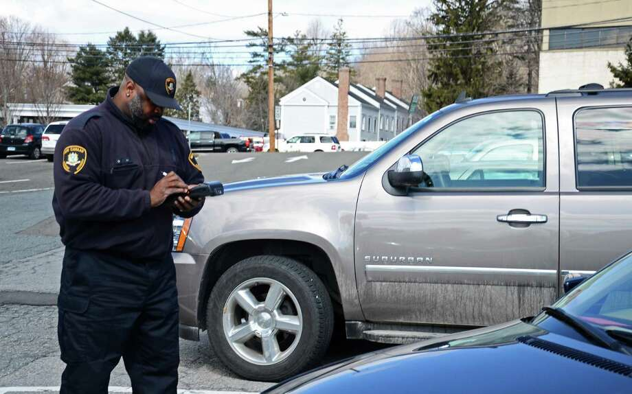 Mike McCargo, a parking enforcement officer in New Canaan, Conn., writes a ticket for a car parked at the Lumberyard lot without a valid permit on March 24, 2014. The town's Parking Bureau will soon have a license plate reader to check for permits. Photo: Nelson Oliveira / New Canaan News