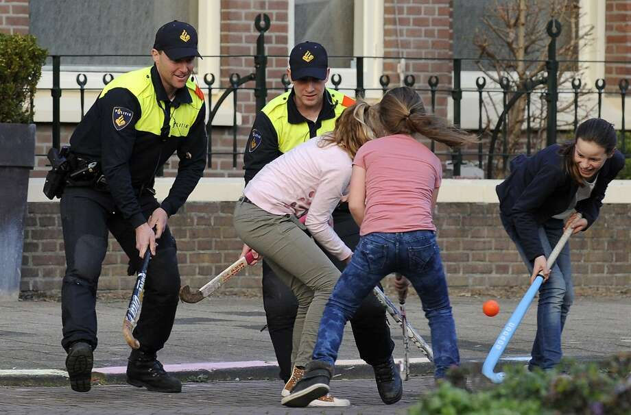 Apparently there's not much crime to fight in the Hague: Policemen play field hockey with girls in a street in the Hague. Photo: John Thys, AFP/Getty Images