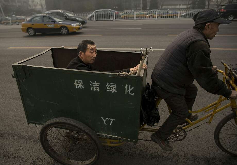 Polluted commute:A Chinese worker man rides to work in the back of a bicycle cart in smoggy Beijing. More than 7 million people die worldwide every year due to air pollution, the U.N. health agency reported. Photo: Kevin Frayer, Getty Images