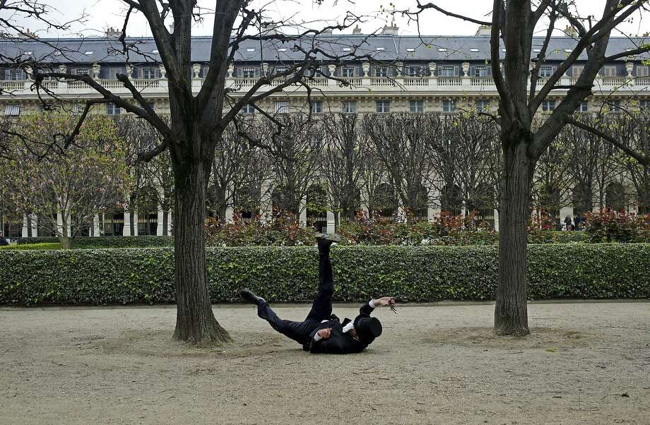 A dapper man tumbles while performing for a short film in the Palais Royal garden of Paris. Photo: Thibault Camus, Associated Press