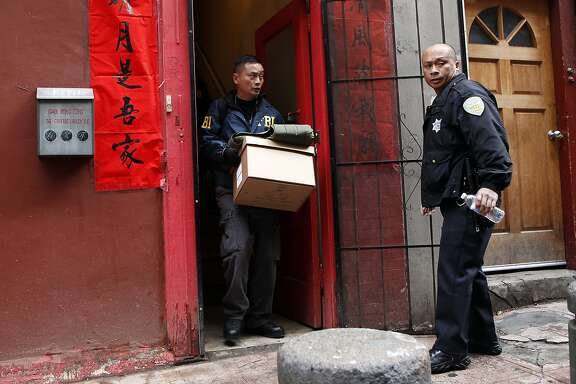 An FBI agent carries boxes of evidence out of the Ghee Kung Tong Chinese Free Masons Temple in Chinatown during a raid related to Sen. Leland Yee's arrest, San Francisco, CA, Wednesday Mar. 26, 2014. The FBI raids State Sen. Leland Yee's office in Sacramento and other locations were searched by the FBI in San Francisco. He was reportedly arrested on public corruption charges Wednesday morning amid raids of his office in Sacramento and searches by the FBI in San Francisco.