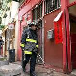 A firefighter carries pry bars and other tools into Ghee Kung Tong Chinese Free Masons Temple in Chinatown during a raid related to Sen. Leland Yee's arrest, San Francisco, CA, Wednesday Mar. 26, 2014.  