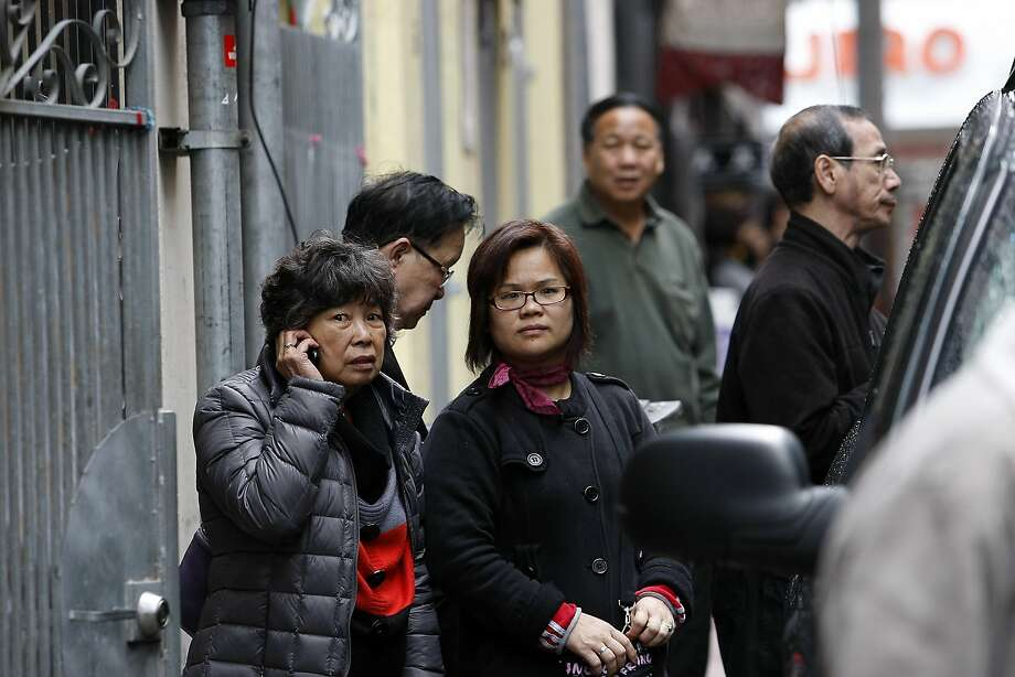 Bystanders watch as police and FBI agents raid the Ghee Kung Tong building in Chinatown. The group was being run as a criminal enterprise, according to the federal affidavit. Photo: Michael Short, The Chronicle