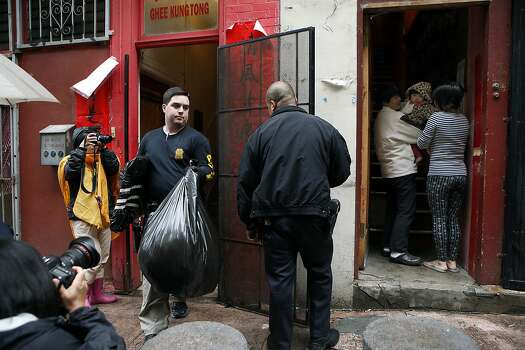 A family stands in their doorway as police carry bags of evidence out of the Ghee Kung Tong headquarters in Chinatown during one of several searches. Photo: Michael Short, The Chronicle