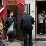 A family,right, stands in their doorway as a Police Special Agent carries bags of evidence out of the Ghee Kung Tong Chinese Free Masons Temple in Chinatown during a raid related to Sen. Leland Yee's arrest, San Francisco, CA, Wednesday Mar. 26, 2014.