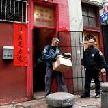 An FBI agent carries boxes of evidence out of the Ghee Kung Tong Chinese Free Masons Temple in Chinatown during a raid related to Sen. Leland Yee's arrest, San Francisco, CA, Wednesday Mar. 26, 2014.