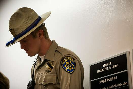 A California Highway Patrol Officer stands guard outside state Senator Leland Yee's office at the State Capitol in Sacramento, California as FBI agents search for evidence inside on March 26, 2014. Photo: Max Whittaker/Prime, Special To The Chronicle