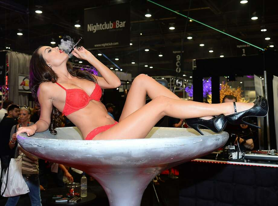 What happens in Vegas ... is often weird:A model lying in a giant golf tee - or possibly champagne glass or birdbath - puffs on a Phantom Smoke hookah at the 29th Nightclub & Bar Convention and Trade Show at the Las Vegas Convention Center. Photo: Ethan Miller, Getty Images For Nightclub & Bar