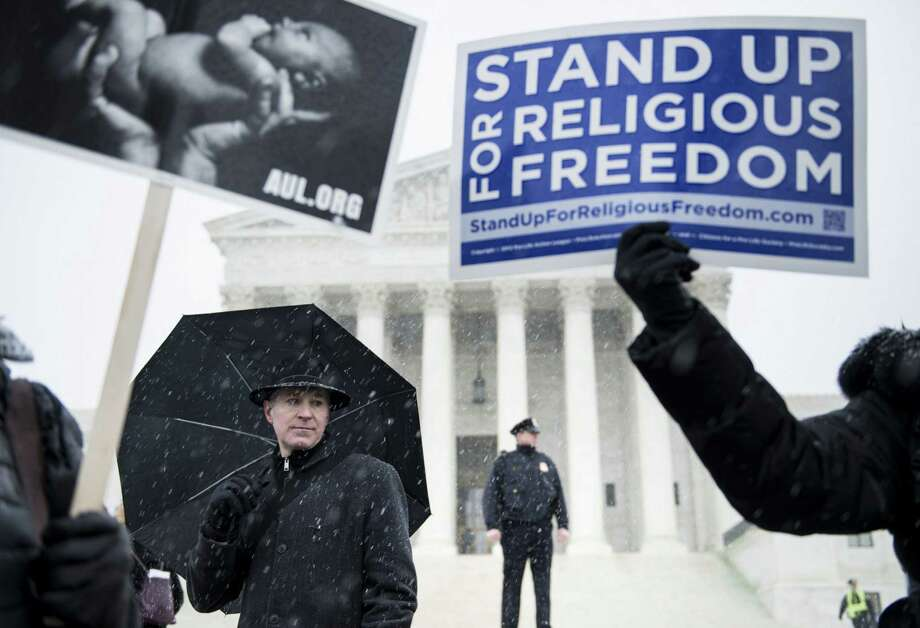 Placards are raised to support Hobby Lobby's choice to withhold coverage for certain forms of contraception  from their employees. The rally was outside the U.S. Supreme Court. Photo: Brendan Smialowski / Getty Images / 2014 Brendan Smialowski