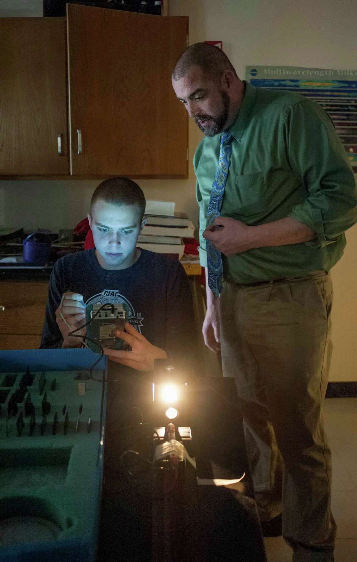 Greenwich high school physics teacher, Dana Schlosser, helps out student Ben Wurst while he works on a project that measures the intensity of light based on the angle of polarization lenses. The class is part of a program called flipped learning an increasingly popular style of learning in which students essentially do homework/assignments in class and then watch or listen to lectures or other forms of teacher instruction at home. Wednesday, March, 26th, 2014.