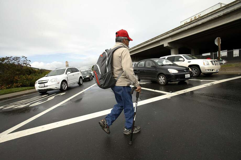 Irineo Camacho, an employee at Golden Gate Fields, crosses the street at the Gilman Street off-ramp from I-80 in Berkeley. Photo: Carlos Avila Gonzalez, The Chronicle