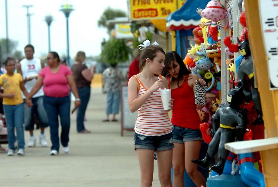 Fairgoers stop to window shop on the midway during the South Texas State Fair at Ford Park in Beaumont, Friday. Tammy McKinley/The Enterprise