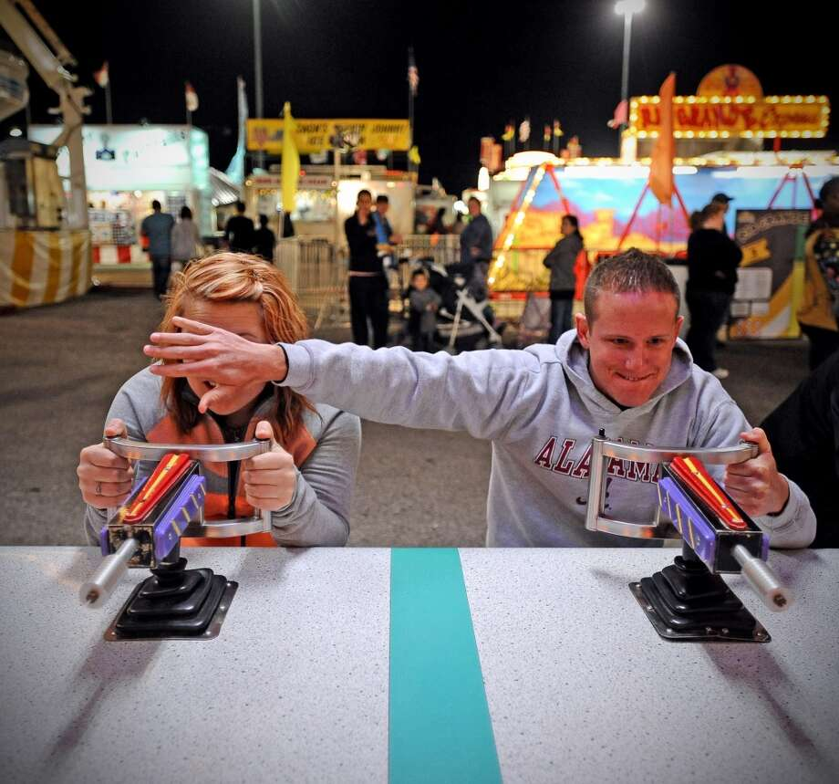 Elayna Mclaughlin and Michael Green of Vidor play the water race at the 70th Annual YMBL Southeast Texas State Fair in Beaumont that opened up Thursday, March 21, 2013. Photo taken: Randy Edwards/The Enterprise