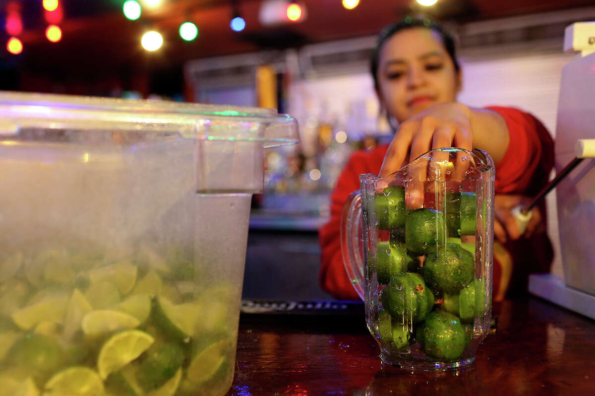 Bartender Cassandra Soto puts limes through a slicer in preparation for customers at Rita's on the River on the River Walk in San Antonio on Wednesday, March 26, 1014.