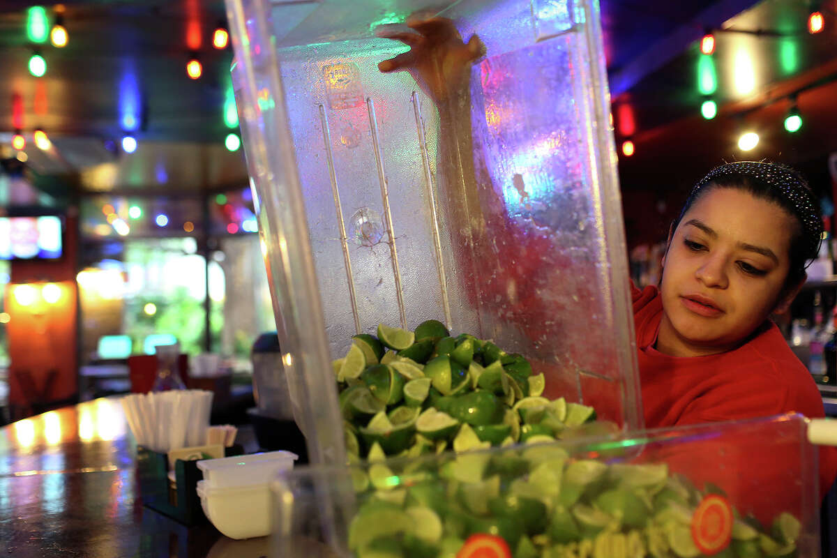 Bartender Cassandra Soto prepares freshly sliced limes for customers at Rita's on the River on the River Walk in San Antonio on Wednesday, March 26, 1014.