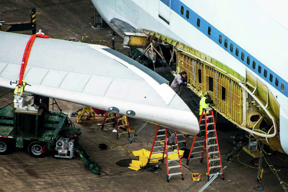 Workers from Boeing remove a wing as they dismantle the NASA Shuttle Carrier Aircraft at Ellington Field. Photo: Smiley N. Pool, Houston Chronicle / © 2014  Houston Chronicle
