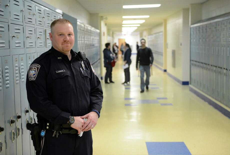 Officer Devin Quintard, one of the school's two resource officers, stands in the halls at Brookfield High School in Brookfield, Conn. on Wednesday, March 26, 2014.  The resource officer program could be in jeopardy because of a dispute between the Brookfield Board of Finance and the Board of Education. Photo: Tyler Sizemore / The News-Times