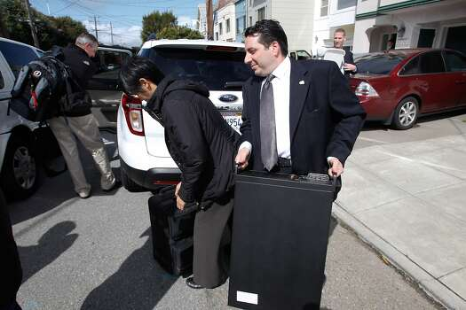 An FBI investigator carries a computer from Yee's house on 24th Avenue in San Francisco during one of the raids. Photo: Mathew Sumner, Special To The Chronicle