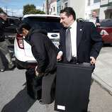 An FBI investigator carries a computer from the house of state Sen. Leland Yee (D-San Francisco) in San Francisco on Wednesday, March 26, 2014. Yee has been arraigned in federal court on charges of public corruption.