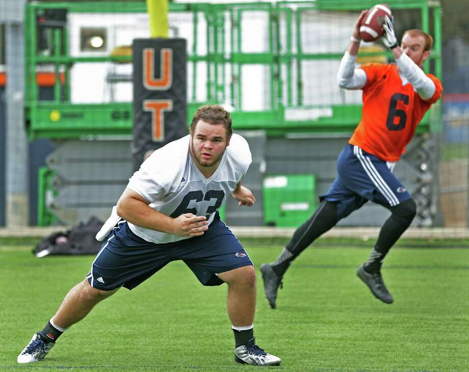 William Cavanaugh, left, hikes to UTSA quarterback Tucker Carter during a recent football practice, Wednesday, March 26, 2014. Cavanaugh is filling in for the injured center Nate Leonard. Photo: BOB OWEN, San Antonio Express-News / © 2012 San Antonio Express-News