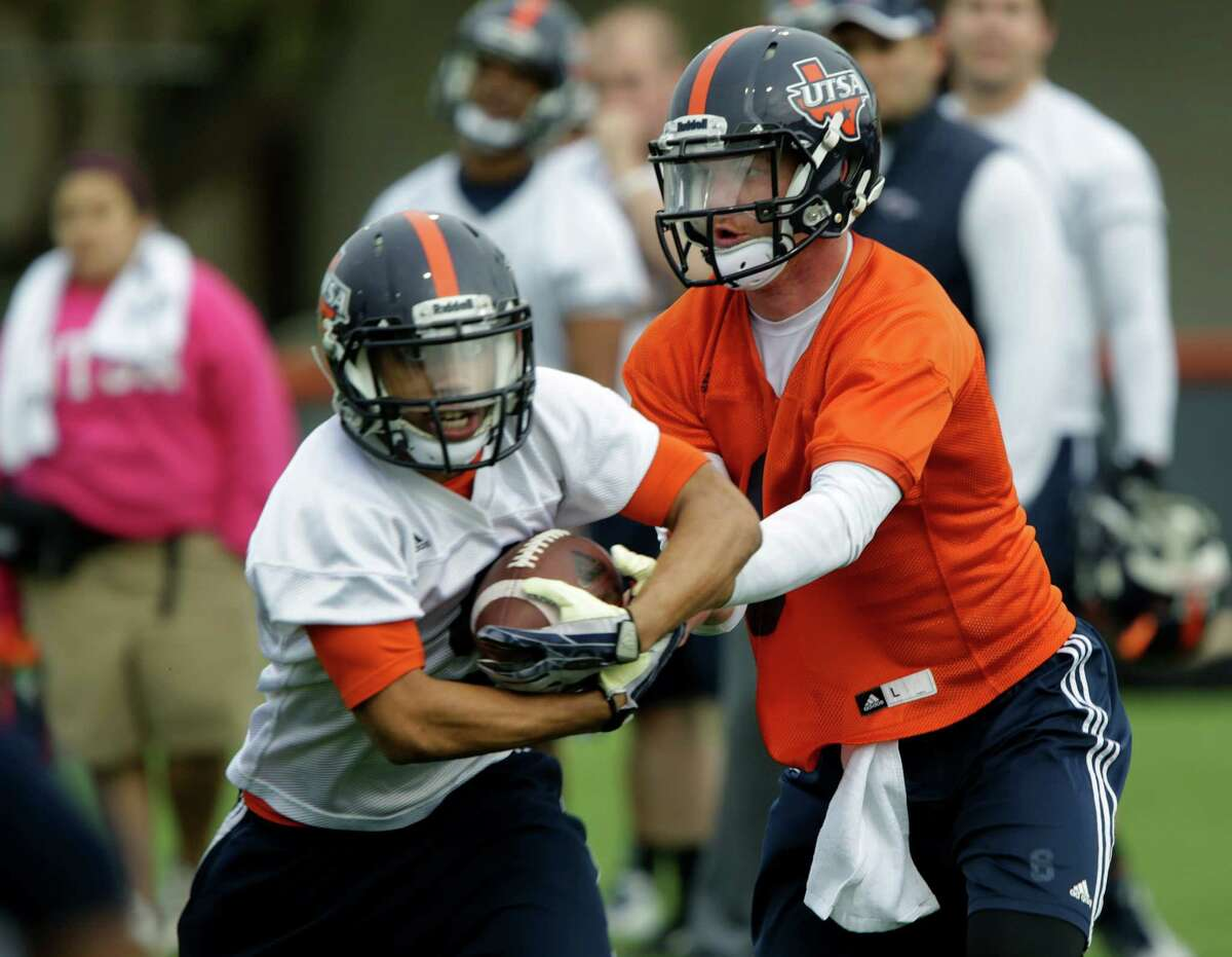 UTSA quarterback Tucker Carter, right, hands off to running back Brandon Armstrong during a UTSA football practice, Wednesday, March 26, 2014.