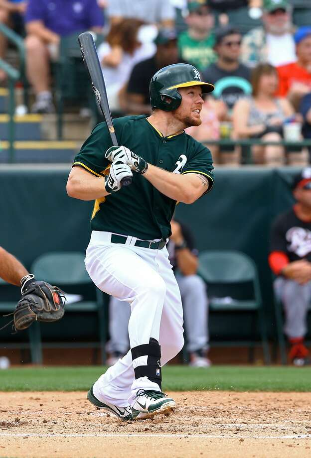 Mar 25, 2014; Phoenix, AZ, USA; Oakland Athletics first baseman Brandon Moss hits a three run home run in the second inning against the Cincinnati Reds at Phoenix Municipal Stadium. Mandatory Credit: Mark J. Rebilas-USA TODAY Sports Photo: Mark J. Rebilas, Reuters