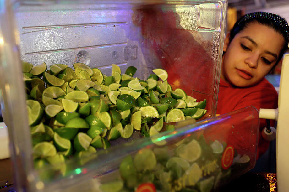Bartender Cassandra Soto prepares freshly sliced limes for customers at Rita's on the River on the River Walk in San Antonio on Wednesday, March 26, 1014. Photo: Lisa Krantz, San Antonio Express-News / SAN ANTONIO EXPRESS-NEWS