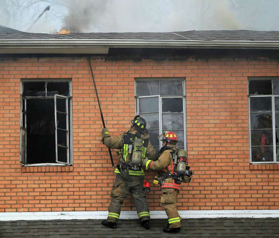 Houston Firefighters work from a first story roof to contain a two-alarm fire at the Heights Presbyterian Church at 240 W 18th Street, Wednesday, March 26, 2014, in Houston. No injuries were reported. The church building is 111-years-old and is home to a small congregation. Photo: Karen Warren, Houston Chronicle / © 2014 Houston Chronicle