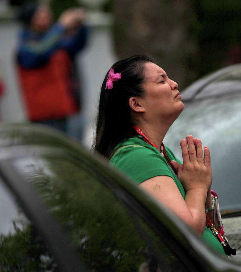 Marybell Gomez prays as Houston Firefighters work to contain a two-alarm fire at the Heights Presbyterian Church at 240 W 18th Street, Wednesday, March 26, 2014, in Houston. Gomez said she attended the church a few times. Photo: Karen Warren, Houston Chronicle / © 2014 Houston Chronicle