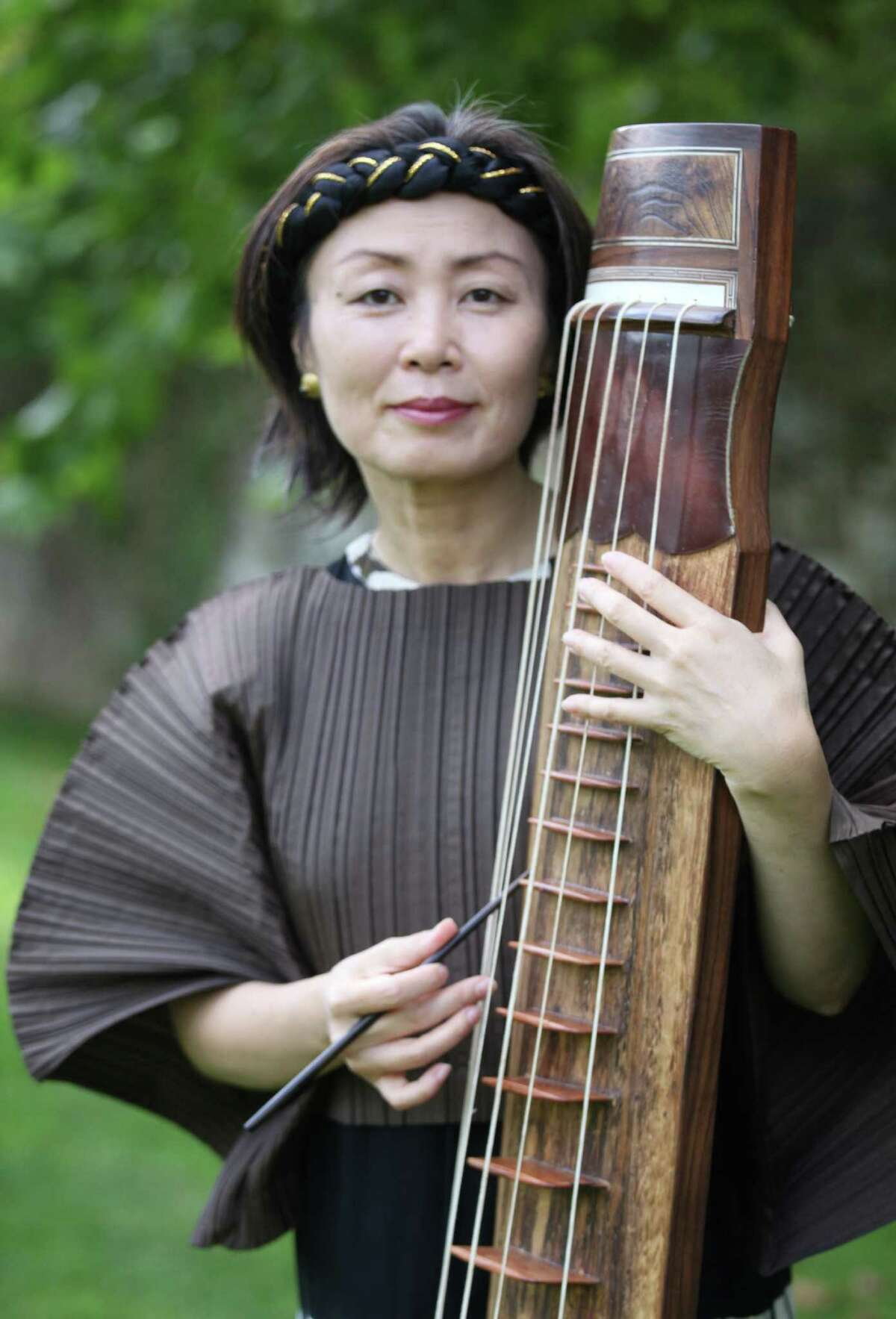A world premiere of a choral work by composer Jin Hi Kim, pictured with her Korean komungo instrument, takes place Sunday, April 6, with the Mendelssohn Choir of Connecticut at Fairfield University. Her