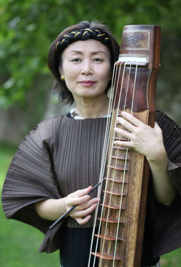 "A world premiere of a choral work by composer Jin Hi Kim, pictured with her Korean komungo instrument, takes place Sunday, April 6, with the Mendelssohn Choir of Connecticut at Fairfield University. Her ""Child of War"" piece explores one of the most horrific, but iconic, photographs from the Vietnam War. Photo: Contributed Photo / Connecticut Post Contributed"