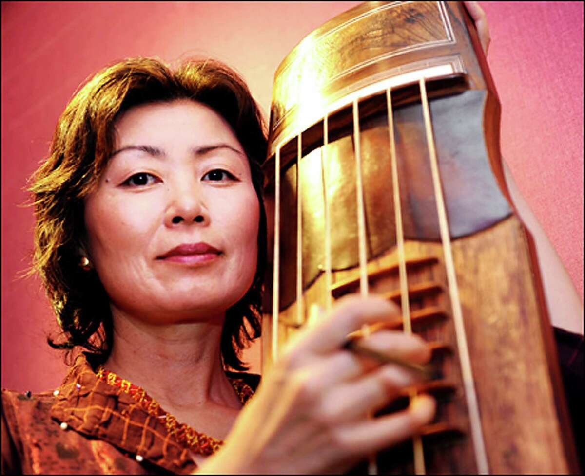 """""""Child of War,"""" a piece by Korean composer Jin Hi Kim, above, will receive its debut with the Mendelssohn Choir of Connecticut on Sunday, April 6, at a """"West Meets East"""" concert at Fairfield University. She also is renowned as a komungo performer and is shown with her instrument."""