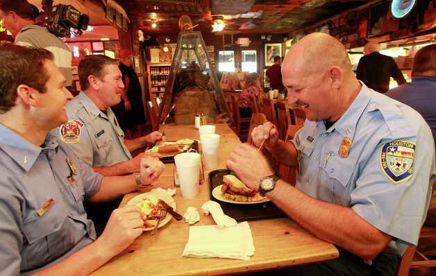 Senior Capt. Brad Hawthorne, right, was on the ladder operated by Dwayne Wyble, center, in Tuesday's rescue. They ate lunch Wednesday with Capt. Jake Sandlin at Goode Co. Barbecue, where the trio paid for their meals despite the restaurant's offer of free sandwiches to all Houston firefighters. (Melissa Phillip/Houston Chronicle)
